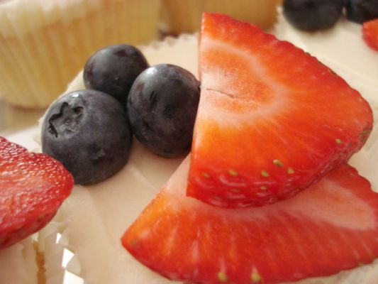 Fresh Berries on top of a Cream cheese frosted vanilla cupcake