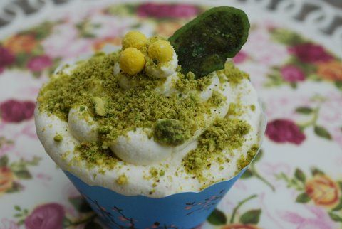 Pistachio Cupcake garnished with candied mint leaf & mimosa flowers