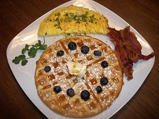 Blueberry waffles with powedered sugar, warm maple syrup, and butter, a cheddar and fresh herbs omelet, and crispy bacon