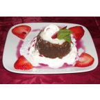 Chocolate and Pecan Molten Lava Cake with Whipped Cream, Strawberries, Powdered Sugar, and a Strawberry and Blueberry Reduction.